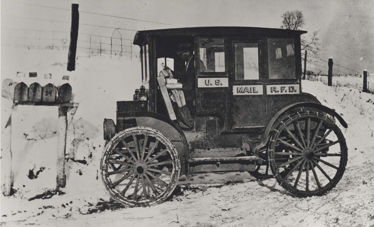 Rural_carrier_in_automobile_at_mailboxes,_c.1910
